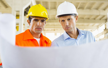 Two men in hardhats reviewing plans