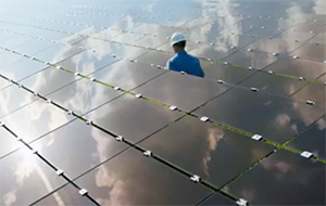 Technician walking through a field of solar panels with clouds reflecting off the panels.